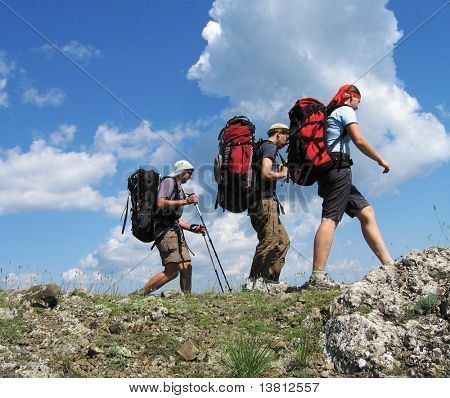 Three climbers going about stone