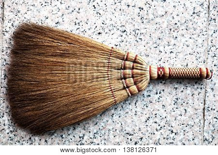 Small whisk/broom for home cleaning on marble floor.