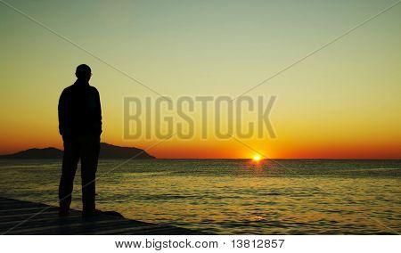 Человек силуэт на закат на море Пир