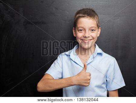 Teenager near blackboard. Child at school. Student at classroom