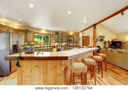 Bright Kitchen Room Interior With Large Wooden Bar And Stainless Steel Fridge.
