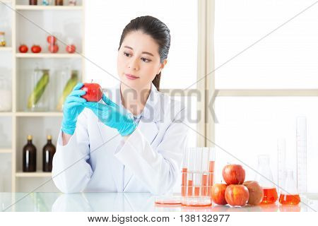 Asian Female Scientist Looking Apple For Genetic Modification Research