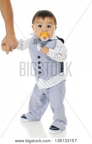An adorable dressed-up baby boy, standing with his mother firmly holding his hand and a
