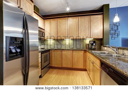 Light Brown Kitchen With Hardwood Floor And Granite.