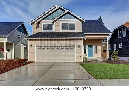 House Exterior. American Beige House With Green Grass.