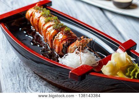 Sushi boat with a shrimp. Sushi rolls and white noodles. Uramaki rolls in soy sauce. Japanese seafood in local restaurant.