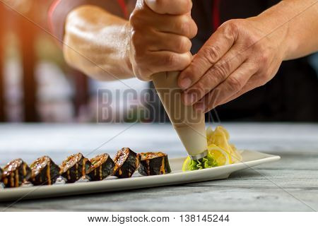 Pastry tool near sushi rolls. Pastry tool puts green wasabi. Hosomaki rolls with spicy wasabi. Worker of japanese restaurant.