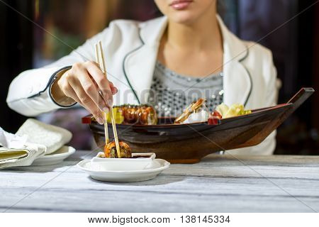 Chopsticks holding a sushi roll. Woman's hand with chopsticks. Lady in japanese restaurant. Bring me your best dish.