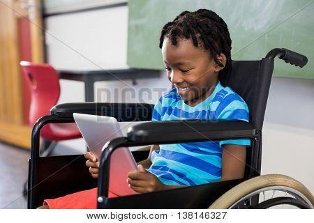 Happy schoolboy sitting on wheelchair and using digital tablet at school