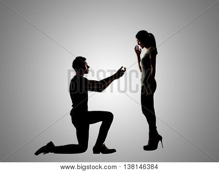 young Asian man propose to his girlfriend, silhouette