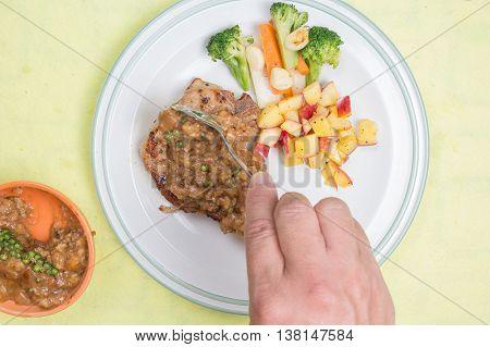 Chef puted gravy sauce to pork chop steak / cooking porkchop steak concept