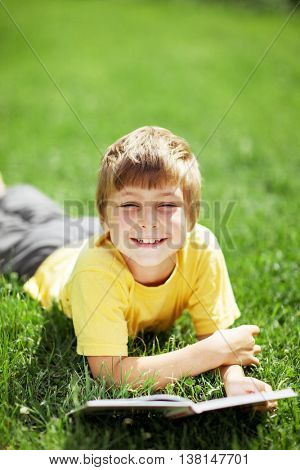 Portrait of cute boy lying on the grass with the book