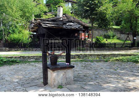 ETAR BULGARIA - JULY 2 2016: Little Caucasian girl at the village well