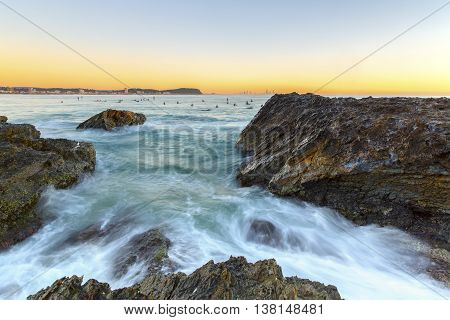 Currumbin Rock Gold Coast clear sky sunrise with incoming ocean rushing against the rocks