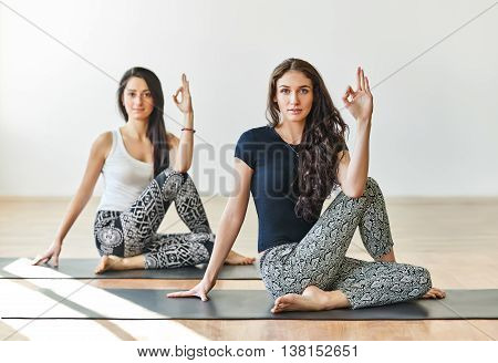 Two Young Women Doing Yoga Asana Half Lord Of The Fishes Pose