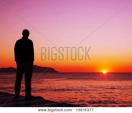 Man silhouette on the sunset on sea pier