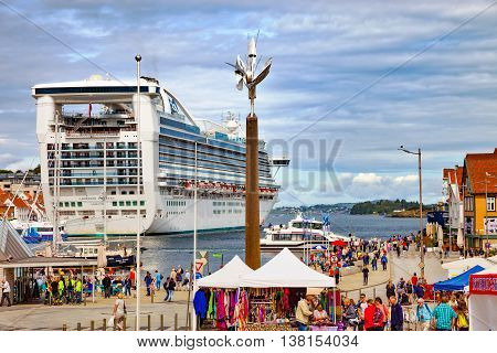 STAVANGER, NORWAY - JULY 13, 2015: People at the quay port with many restaurants and pubs in the city centre. Stavanger is one of most famous cruise travel destinations in Europe.