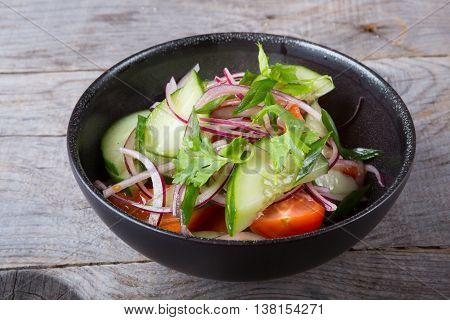 Mixed vegetables salad served in a blach bowl