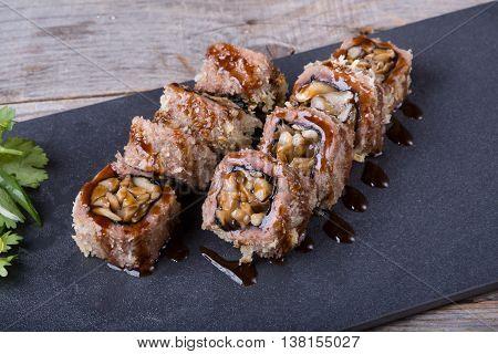 Japanese mushrooms rolls snack served with unagi sauce