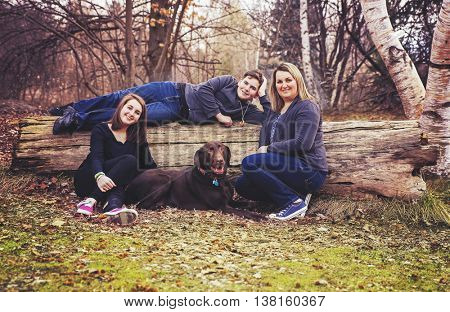 a family sitting with their dog, a chocolate lab in a park on a tree trunk log toned with a retro vintage filter instagram app or action effect