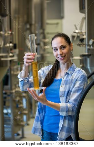 Portrait of beautiful female brewer hydrometer cylinder at brewery factory
