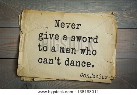 Ancient chinese philosopher Confucius quote on old paper background. Never give a sword to a man who can't dance.