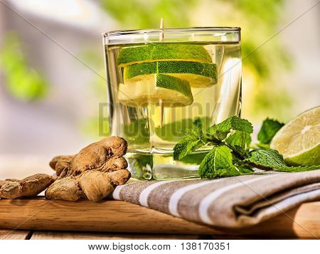 Healthy detox drink with ginger . On wooden boards glass with lime green tea and mint. Mint ginger drink number hundred six with half and slice lime and striped napkin. Country life. Light background.