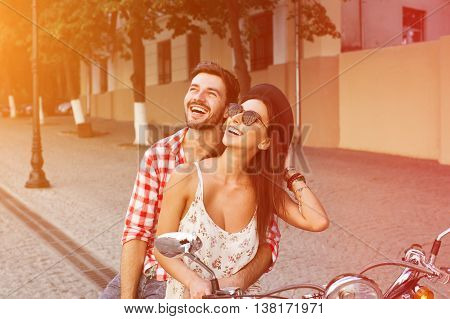 glamorous  young couple sitting on a vintage scooter in the street, man wears a shirt and the woman - a summer dress and sunglasses