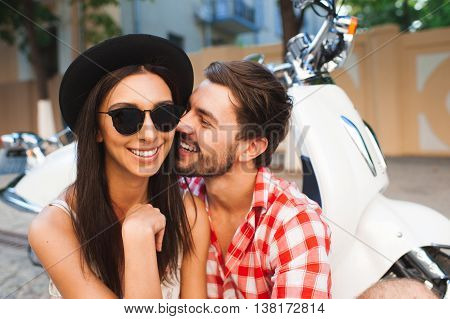Hipster young couple traveling with vintage scooter. Young man hugging his girlfriend on scooter background