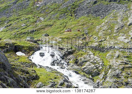 GEIRANGERFJORD, NORWAY - JUNE 29: Tourists on a viewing platform near the Trollstigen road between the mountains on June 29, 2016 in Geiranger, Norway. Geirangerfjord is UNESCO heritage site.