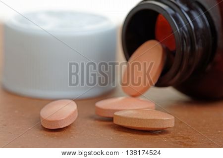 Statins or generic pills pouring from a bottle. Close up with shallow depth of field