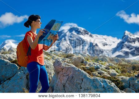 female hiker with backpack and map standing on the trail against snow-covered big mountains and blue sky at early morning and looking to the map.