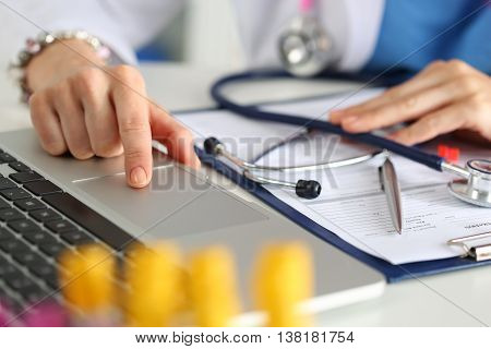 Close up view of female medicine doctor or student hands working on laptop. Physician or intern working at laboratory or hospital office room. Therapeutist sit at working table making some paperwork