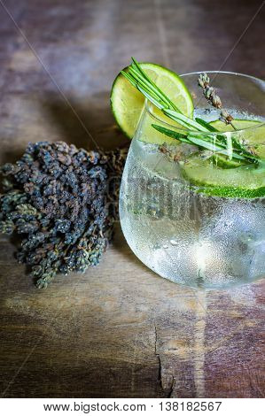 Detox beverage with fresh lime and rosemary on rustic background poster