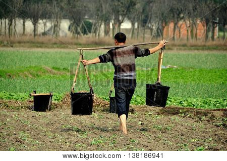 Jiu Chi Town China - October 25 2012: Farmer at work watering newly set out plants in a field at his farm