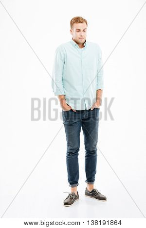 Full length of shy embarrassed young man standing with hands in pockets over white background