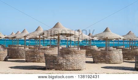 thatched umbrellas on a tropical beach near sea