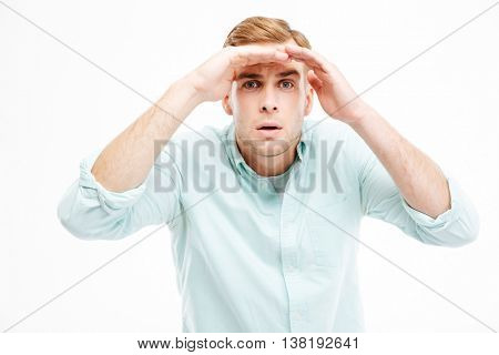 Serious young businessman straring and looking far away over white background