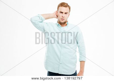 Pensive handsome young man thinking and scratching his head over white background