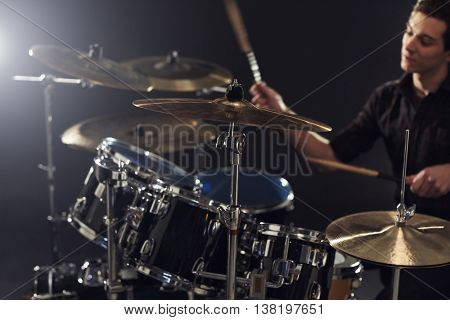 Side View Of Young Drummer Playing Drum Kit In Studio