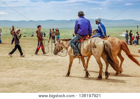 Khui Doloon Khudag Mongolia - July 12 2010: Horseback riders at Nadaam (Mongolia's most important festival whose roots lie in Mongolian warrior traditions) horse race near capital Ulaanbaatar.