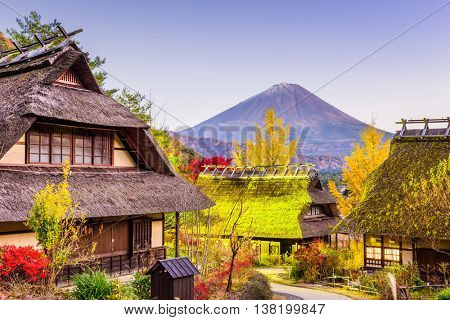 Mt. Fuji, Japan with historic village Iyashi no Sato during an autumn twilight.