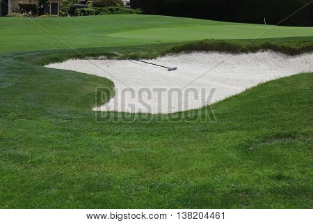 White sand trap with rake lying down in the sand surrounded by the green grass of the golf course
