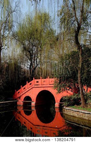 Pixian China - February 23 2009: Weeping willows with Spring leaves and a beautiful three arched bridge over the lagoon in Wang Cong Ci Park