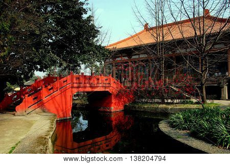 Pixian China - February 23 2009: A beautiful orange Chinese bridge and the great temple prayer hall at Wang Cong Ci Park