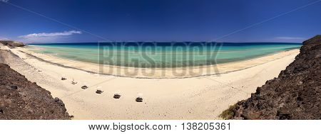 View to sandy beach with vulcanic mountains in the background near Costa Calma town on Fuerteventura island Canary Islands Spain.