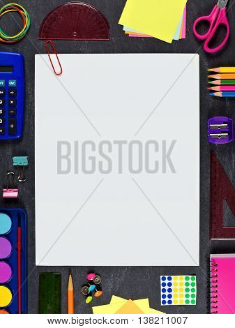 Blank White Paper With Paper Clip And Frame Of School Supplies Over A Chalkboard Background