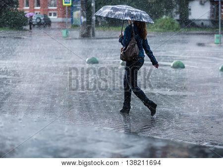 Woman with umbrella going on street during heavy rain rain
