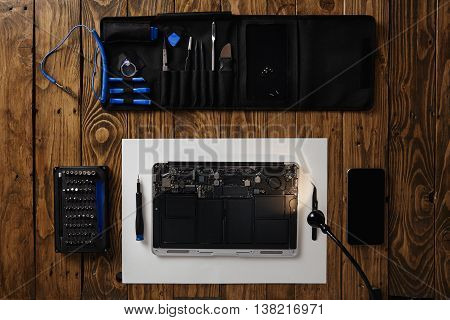 Top view on cleaned and repaired laptop computer isolated on vintage wooden table near professional tools and smartphone before assembling back