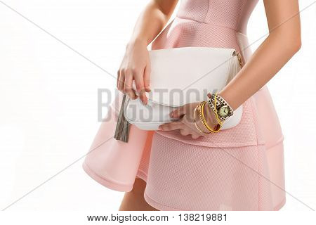 Girl's hands with white purse. Yellow bracelets and small watch. Nice clothes and stylish accessories. Salmon dress for summer.